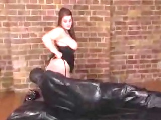 giant beautiful woman domme tortures rubber clad